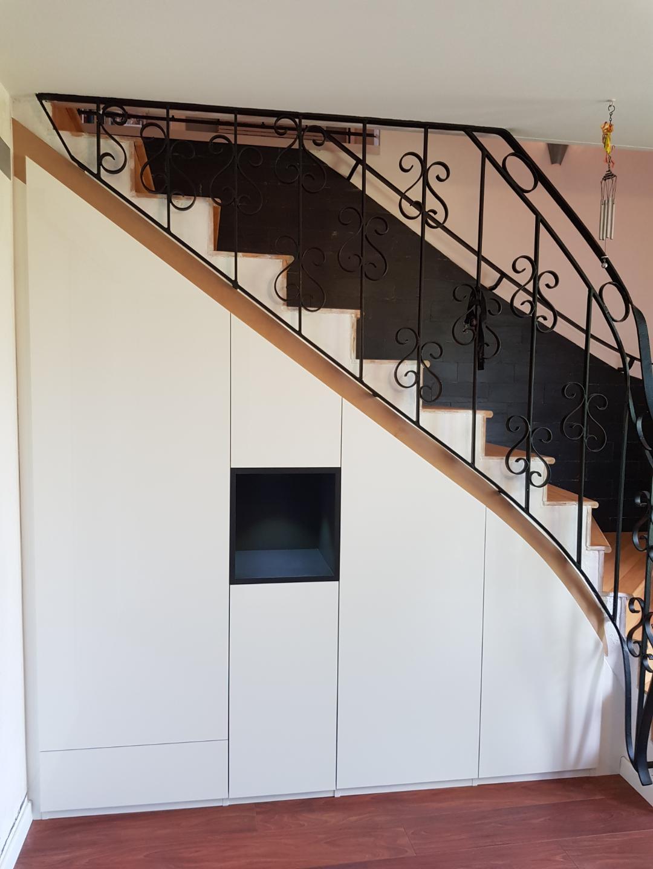 Aménagement sur-mesure sous-escalier blanc et niche ouverte bleue